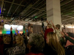 Women raised hands in support during the One Billion Rising video presentation. The video shows women around the world support each other while they are treated violently. (Kjersten Johnson)