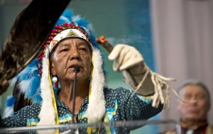 In this photo taken on Thursday, Oct. 15, 2015, Larry Cesspooch of the Ute Tribe leads a prayer in the opening plenary at the Parliament of the World's Religions held inside the Salt Palace Convention Center in Salt Lake City. Visitors from 80 countries and 50 different religions arrived in Salt Lake City to attend the interfaith conference being held in the United States for the first time since 1993. (Lennis Mahler/The Salt Lake Tribune via AP) DESERET NEWS OUT; LOCAL TELEVISION OUT; MAGS OUT; MANDATORY CREDIT