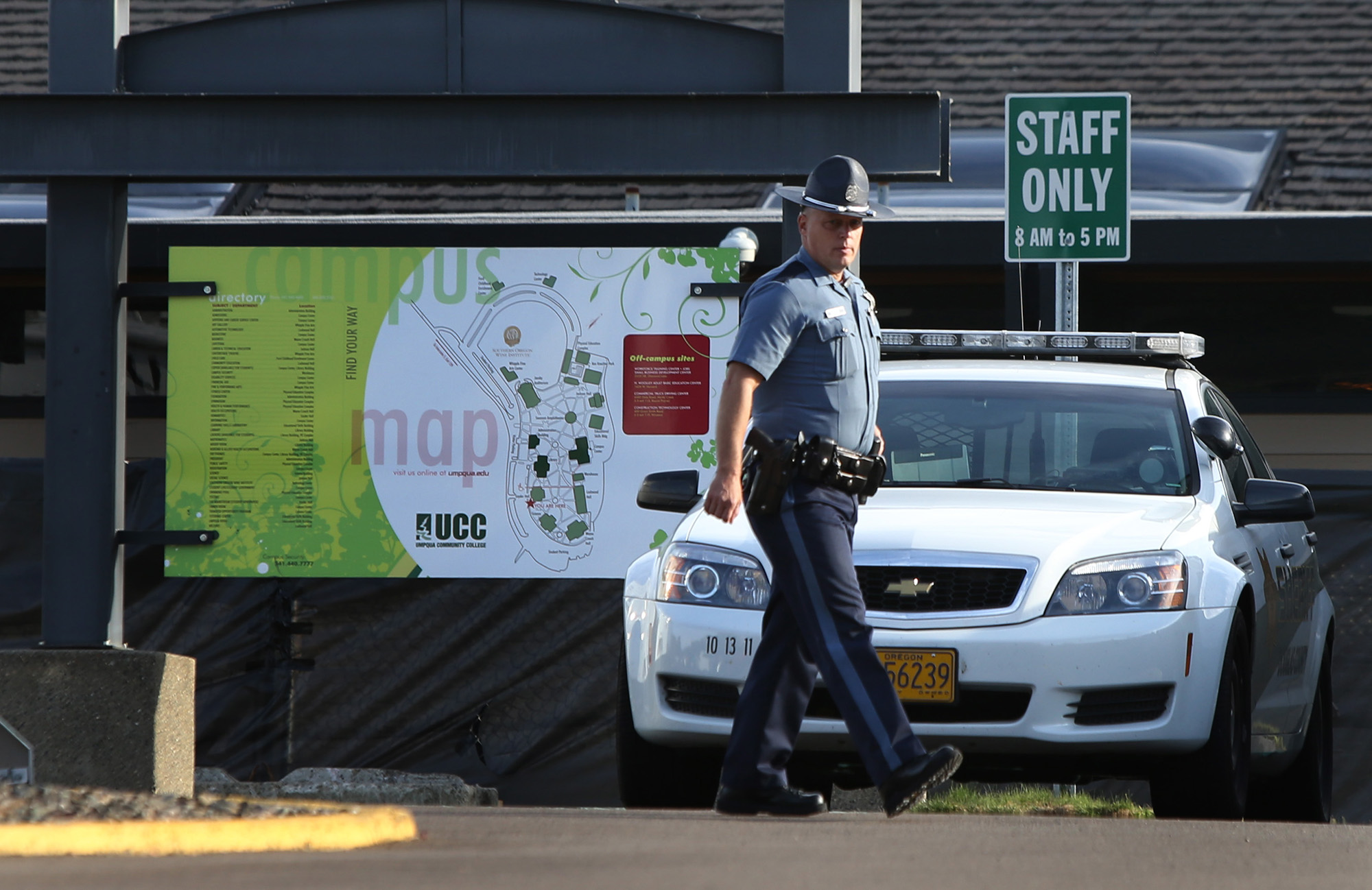 An Oregon State Patrol Trooper walks the grounds of Umpqua Community College near Roseburg, Ore. Tuesday Oct. 6, 2015 in the aftermath of the mass shooting on the Roseburg campus. (Chris Pietsch/The Register-Guard via AP)