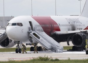 Firefighters walk past a Dynamic Airways Boeing 767, Thursday, Oct. 29, 2015, at Fort Lauderdale/Hollywood International Airport in Dania Beach, Fla. The passenger planes' engine caught fire Thursday as it prepared for takeoff, and passengers had to quickly evacuate on the runway using emergency slides, officials said. The plane was headed to Caracas, Venezuela. (AP Photo/Wilfredo Lee)