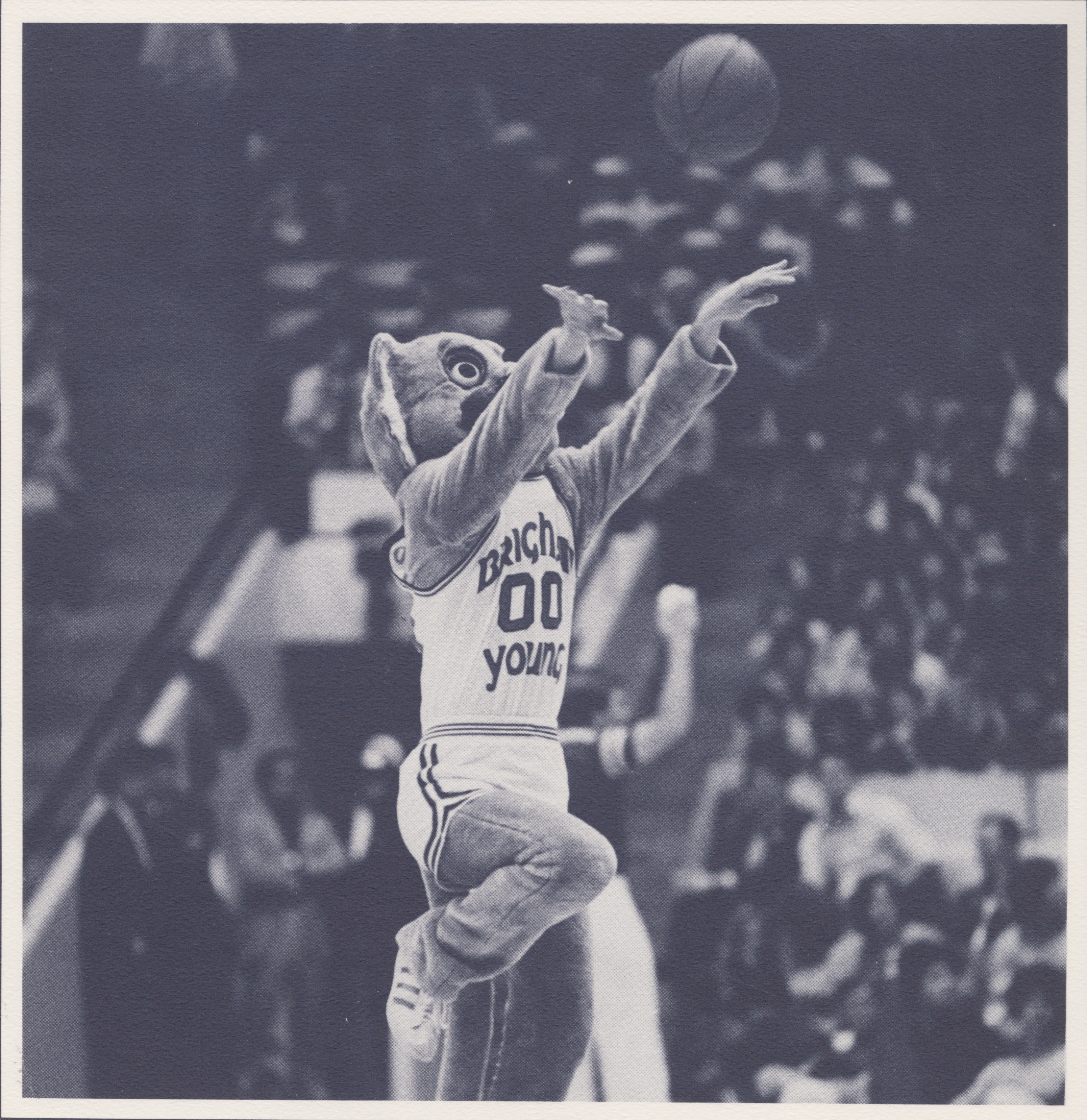 Cosmo takes a half-court shot during a game in the 1980-81 basketball season. Cosmo is an entertainer at any appearance he makes. (L. Tom Perry Special Collection)