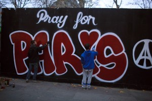 """Two men paint a mural reads: """"Pray for Paris"""" in tribute to the victims of the Paris attacks, in Paris, Saturday Nov. 14, 2015. French President Francois Hollande vowed to attack Islamic State without mercy as the jihadist group admitted responsibility Saturday for orchestrating the deadliest attacks inflicted on France since World War II. (AP Photo/Thibault Camus)"""