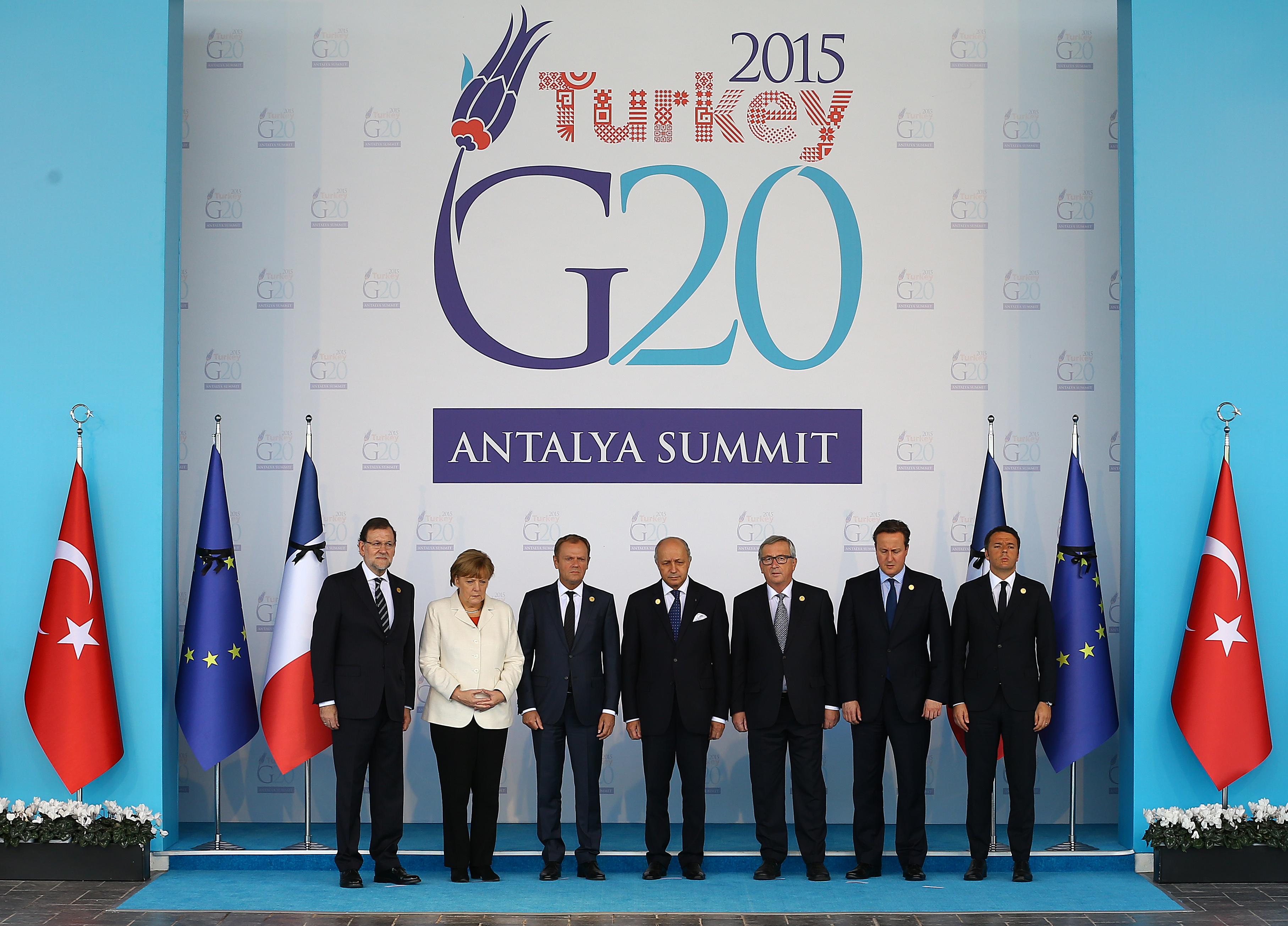 European Union leaders observe a minute of silence to honour the victims of the attacks in Paris, at the G-20 Summit in Antalya, Turkey, Monday, Nov. 16, 2015. From left to right, Spain's Prime Minister Mariano Rajoy, German Chancellor Angela Merkel, European Council President Donald Tusk, France's Foreign Minister Laurent Fabius, European Commission President Jean-Claude Juncker, British Prime Minister David Cameron, and Italian Prime Minister Matteo Renzi. The leaders of the Group of 20 were wrapping up their two-day summit in Turkey Monday against the backdrop of heavy French bombardment of the Islamic State's stronghold in Syria. (Anadolu Agency via AP, Pool)