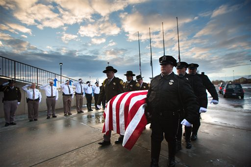 Unified Police Department officer Doug Barney's casket is carried into the arena prior to his funeral at the Maverik Center in West Valley City, Utah, Monday, Jan. 25, 2016. Barney was killed in the line of duty on Sunday, Jan. 17. (Scott G Winterton/Deseret News via AP))