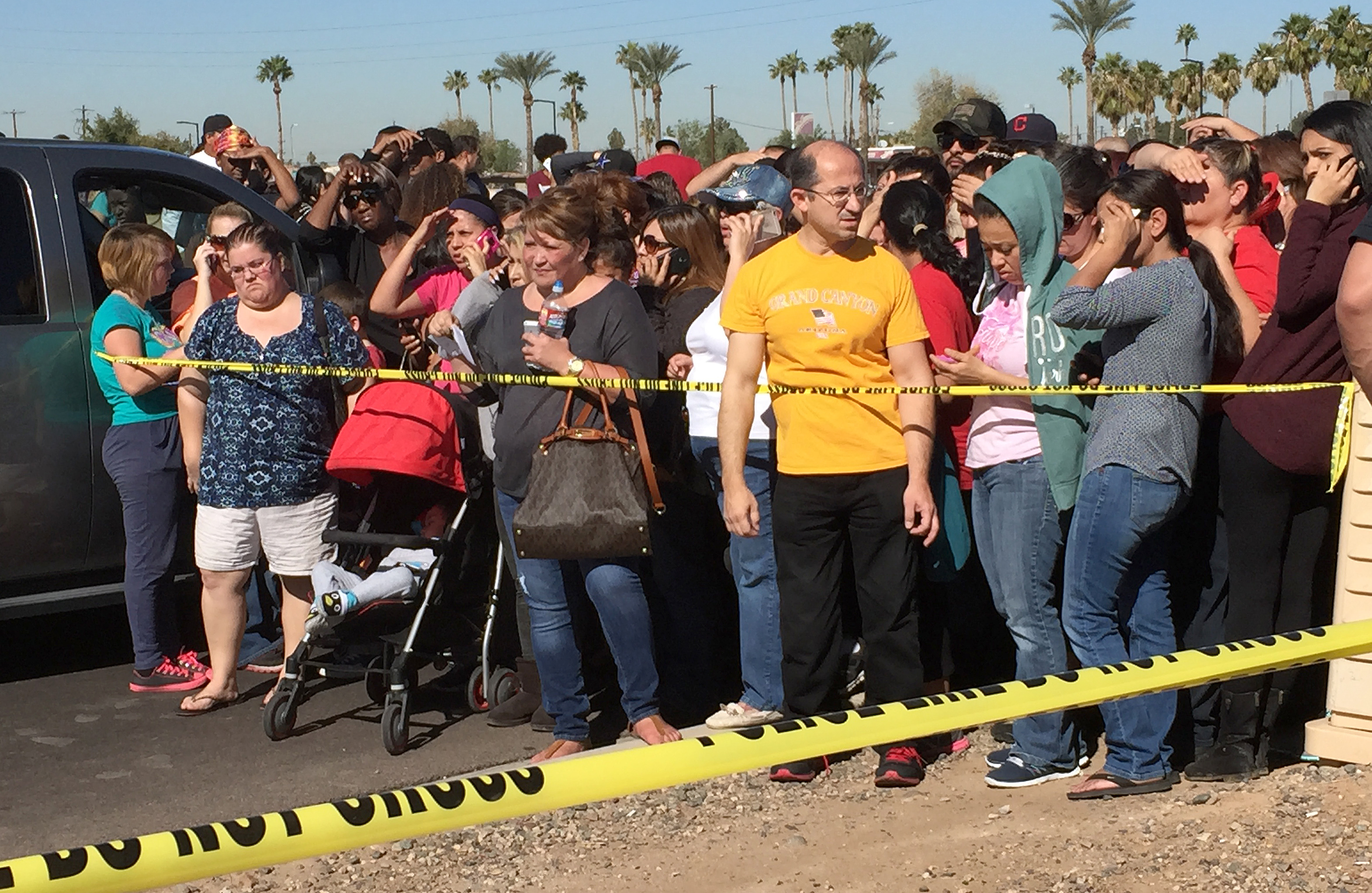 Parents and others wait near a high school in Glendale, Ariz., to be reunited with students after police say two female students died in a shooting at the school in a Phoenix suburb. (AP Photo/Matt York)