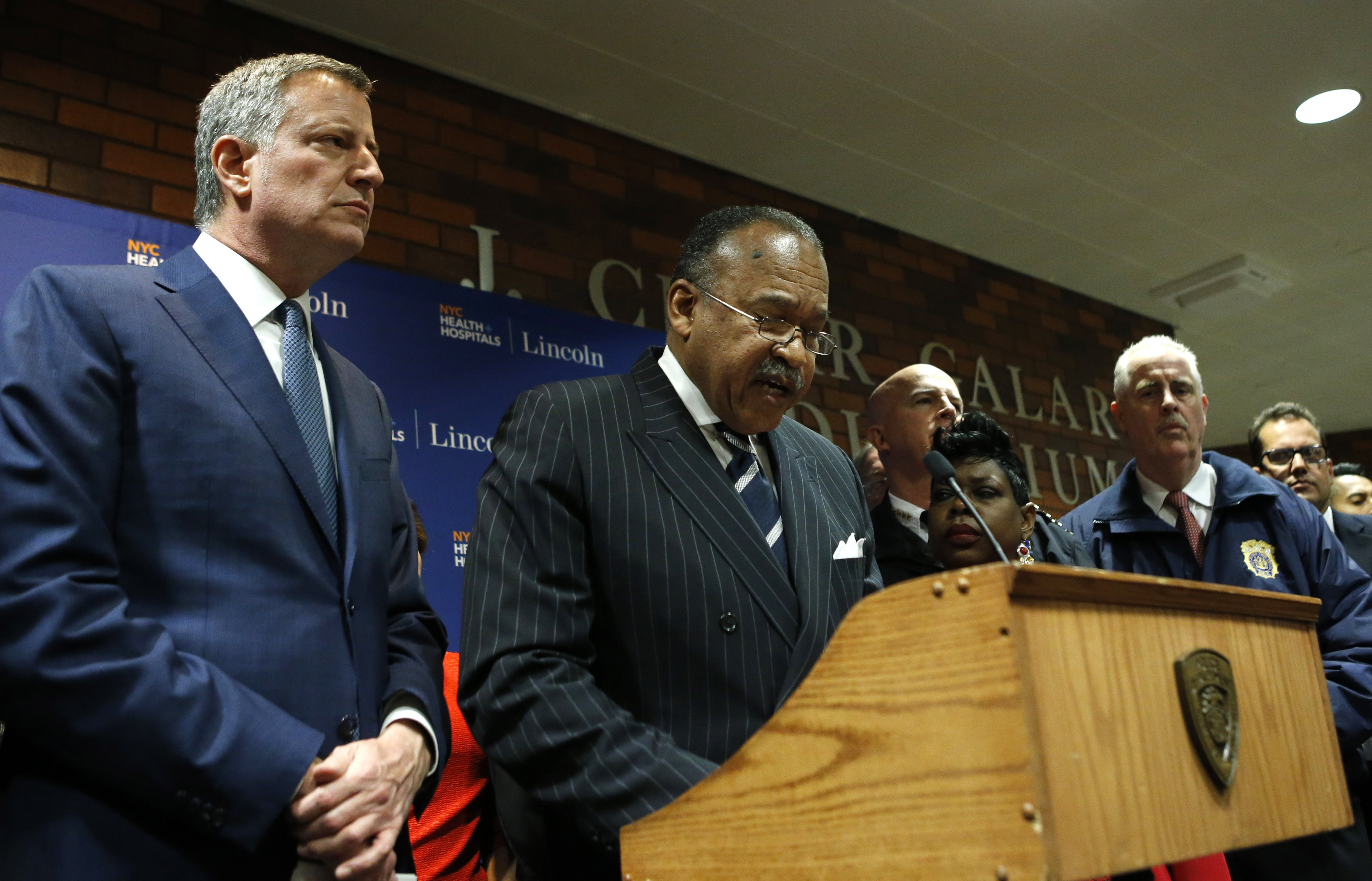 CORRECTS ID OF MAN AT RIGHT TO NYPD CHIEF OF DETECTIVES ROBERT BOYCE, NOT JAMES O'NEILL - New York City Mayor Bill de Blasio listens as New York City Police First Deputy Commissioner Benjamin Tucker speaks at a hastily called press conference at Lincoln Hospital, Thursday, Feb. 4, 2016, in the Bronx borough of New York after two New York City police officers were shot in a public housing complex int he Bronx by an armed suspect who apparently turned the weapon on himself not far from where de Blasio was delivering his state of the city address Thursday evening. New York City Police Department Chief of Detectives Robert Boyce, listens, right. (AP Photo/Kathy Willens)