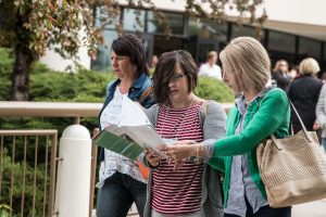 Two conference attendees review the class schedule for the 2016 Women's Conference outside the Marriott Center. (Maddie Dayton)