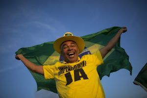 An anti-government demonstrator celebrates the result of the impeachment process outside Congress in Brasilia, Brazil, Thursday, May 12, 2016. Brazil's Senate voted Thursday to impeach President Dilma Rousseff just months before it hosts the Summer Olympics. Rousseff's ally-turned-enemy, Vice President Michel Temer, will take over as acting president later Thursday while she is suspended. The Senate has 180 days to conduct a trial and decide whether Rousseff should be permanently removed from office. (AP Photo/Felipe Dana)