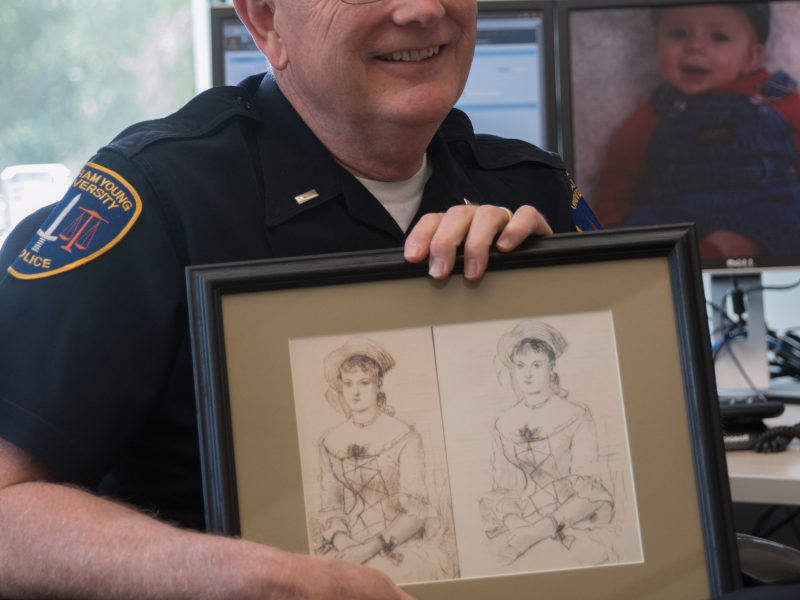 """Lt. Arnold Lemmon holds his copy of the forged and original Winslow Homer sketch, """"The Shepherdess."""" Lemmon worked on retrieving over 900 missing pieces of BYU-owned art during his  career. (Natalie Stoker)"""