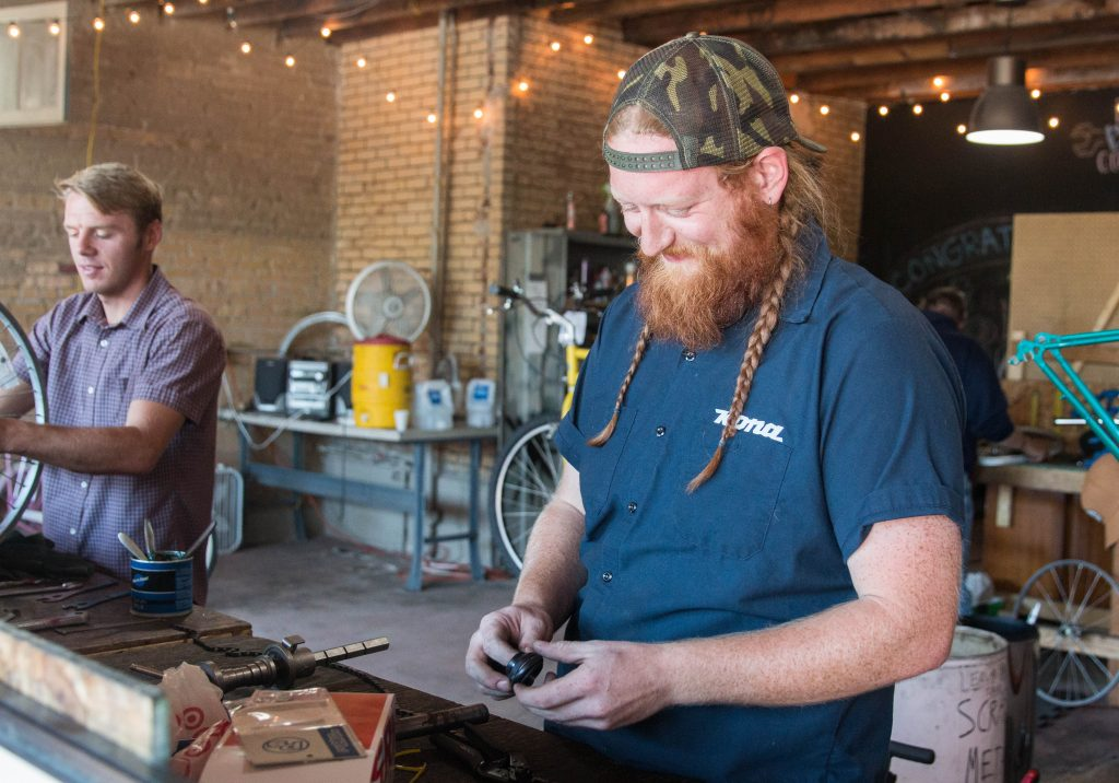 Kai Cox, pictured on the right, and Kyle Owens both enjoy fixing bikes for the Provo Bicycle Collective.