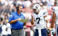 Offensive coordinator Ty Detmer discusses a play call with quarterback Taysom Hill. (BYU Photo)