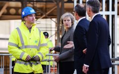 Britain's Prime Minister Theresa May and Chancellor of the Exchequer Philip Hammond, right, during a visit to a construction site in Birmingham, England, where new HSBC bank offices are being built, Monday Oct. 3, 2016. May announced Sunday a timetable for Britain's exit from the European Union, and Treasury chief Hammond warned on Monday of turbulence in the coming years as Britain negotiates its exit from the trading bloc. (Stefan Rousseau / PA via AP)