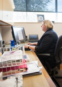 Dean Prater takes a break from moving into her new office to get some work done.