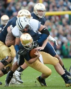 BYU defensive lineman Bronson Kaufusi sacks Notre Dame quarterback Tommy Rees. Photo by Chris Bunker
