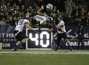Quarterback Taysom Hill leaps between two defenders against Boise State. Hill threw for three touchdowns and ran for another as the Cougars defeated the Broncos 37-20.