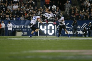 Taysom Hill jumps with the ball in attempt to leap over two Boise State defenders.