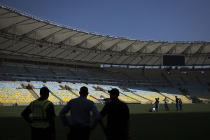 Workers paint white lines on the grass during an inspection tour of Maracana stadium in Rio de Janeiro, Brazil. AP Photo.