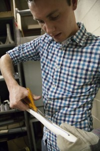 Adam Barlow cuts a heated PVC pipe in preparation for making a prosthetic leg. (Photo by Elliott Miller)