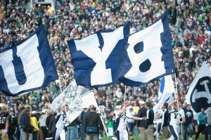 BYU cheerleaders lead the football team onto the field before a game. (Universe Photo)