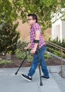 Zayne Callahan walks across the BYU campus. Callahan was born with spina bifida, but after undergoing surgery, was able to begin walking with the help of crutches. (Elliot Miller)