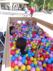 "Students socialize in the October ball pit at Brigham Square. They ask each other questions written on the balls like, ""how old are you?"" and ""what is your best scar story?"" (Cara Wade)"