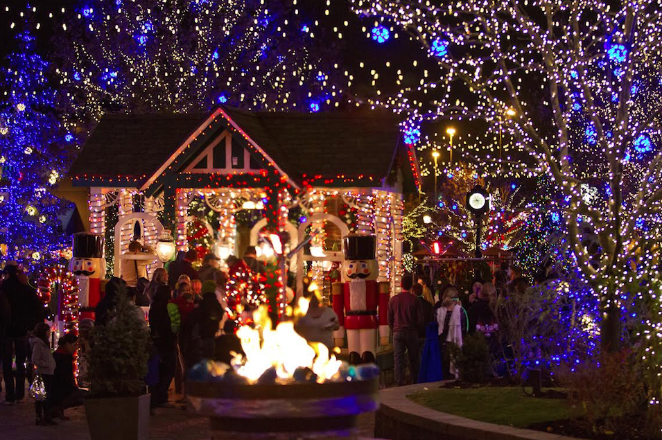 Visitors at the shops at the Riverwoods stay warm by the fire in the line to - Christmas Lights Displays Warm Residents Up For The Holidays - The