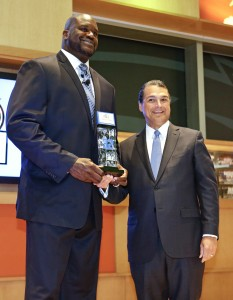 Orlando Magic CEO Alex Martins, right, presents former NBA player Shaquille O'Neal an award during a ceremony inducting him in the Magic Hall of Fame, Friday, March 27, 2015, in Orlando, Fla. Selected by Orlando with the first overall pick of the 1992 NBA Draft, O'Neal spent four seasons with the Magic from 1992-96. (AP Photo/John Raoux)