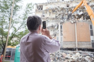 Onlookers take photos and videos of the demolition. The high-reach demolition machines are strong enough to tear apart steal beams inside the building. (Maddi Dayton)