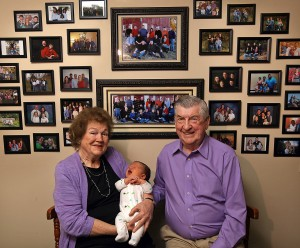 """In this April 17, 2015 photo, Leo and Ruth Zanger sit with their 100th grandchild, Jaxton Zanger, in Leo's real estate office in Quincy, Ill. Jaxton was born April 8 to parents Austin and Ashleigh Zanger. For the numerically inclined, Jaxton was also No. 46 among the great-grandchildren. The Zangers also have 53 grandkids and one great-great-grandchild for a nice round 100. """"The good Lord has just kept sending them,"""" Leo Zanger said of the grandkids. """"We could start our own town."""" (Phil Carlson/The Quincy Herald-Whig via AP)"""