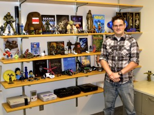 Dr. Kevin John shows off his sizeable collection of video game memorabilia. John's young age helps him relate to his students. (Taylor Ricks)