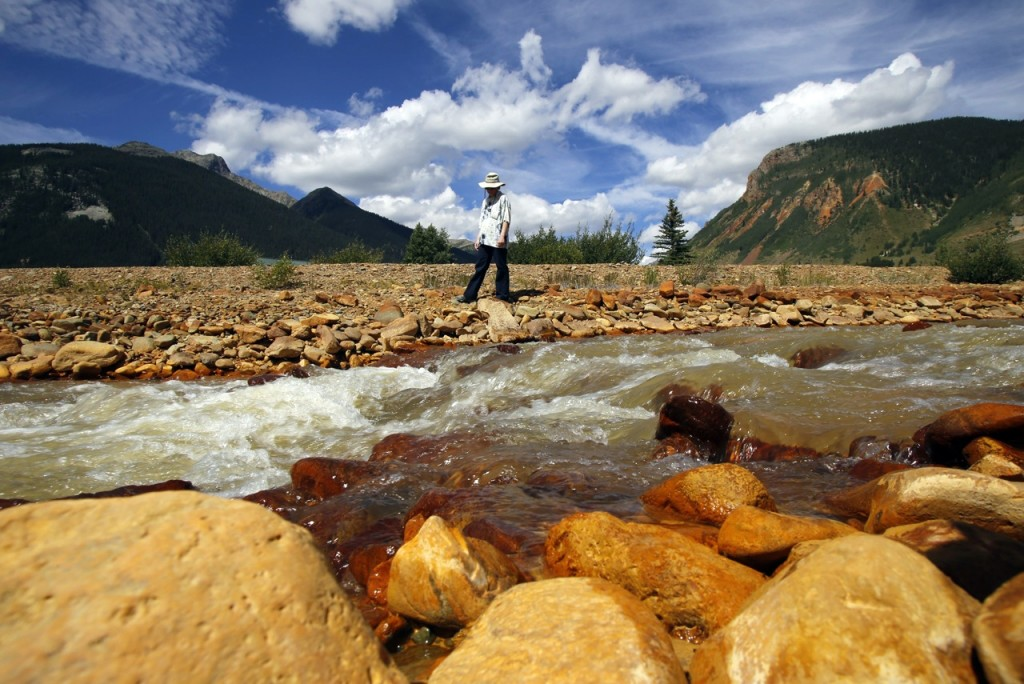 FILE - In this Aug. 10, 2015, file photo, Silverton, Colo., resident Melanie Bergolc walks along the banks of Cement Creek in Silverton, polluted by mine waste runoff. The focus on a toxic mine spill that fouled rivers in three states shifts to Congress the week of Sept. 7 as lawmakers kick off a series of hearings into how the U.S. Environmental Protection Agency accidentally unleashed the deluge of poisoned water. (Jon Austria/The Daily Times via AP, File) MANDATORY CREDIT