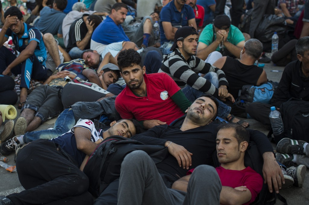 Migrants and refugees wait to be registered by police at the port of Mytilene, on the Greek island of Lesbos, early Sunday, Sept. 6, 2015. (AP Photo/Santi Palacios)