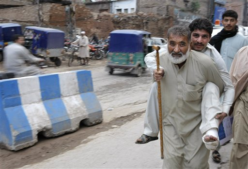 A Pakistani carries a man who was injured from an earthquake in Peshawar, Pakistan, Monday, Oct. 26, 2015. A powerful 7.7-magnitude earthquake in northern Afghanistan rocked cities across South Asia. Strong tremors were felt in Kabul, New Delhi and Islamabad on Monday. In the Pakistani capital, walls swayed back and forth and people poured out of office buildings in a panic, reciting verses from the Quran. (AP Photo/Mohammad Sajjad)
