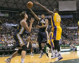 Utah Jazz guard Trey Burke (3), center, goes between Utah Jazz guard Olivier Hanlan (21), left, and Los Angeles Lakers center Roy Hibbert (17) during the second half of an NBA preseason basketball game, Tuesday, Oct. 6, 2015, in Honolulu. The Jazz defeated the Lakers 117-114. (AP Photo/Marco Garcia)
