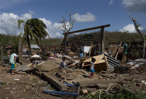 Residents walk through the debris of homes destroyed by Hurricane Patricia, in Chamela, Mexico, Saturday, Oct. 24, 2015. Record-breaking Patricia pushed rapidly inland over mountainous western Mexico early Saturday, weakening to tropical storm force while dumping torrential rains that authorities warned could cause deadly floods and mudslides. (AP Photo/Rebecca Blackwell)