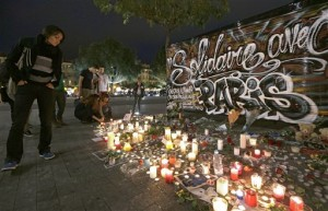 """People pay tribute to the victims of the terror attacks in Paris by a poster which reads """"Solidarity with Paris"""" in Nice, southeastern France, Monday, Nov. 16, 2015. France is urging its European partners to move swiftly to boost intelligence sharing, fight arms trafficking and terror financing, and strengthen border security in the wake of the Paris attacks. (AP Photo/Lionel Cironneau)"""