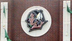 The University of North Dakota's Fighting Sioux logo hangs on Ralph Engelstad Arena in Grand Forks, N.D. The school adopted the nickname the Fighting Hawks on Wednesday, Nov. 18, 2015, to replace the Fighting Sioux. Students across the United States are pressuring their colleges to update mascots, mottos and building names that they say are insensitive. (Associated Press)