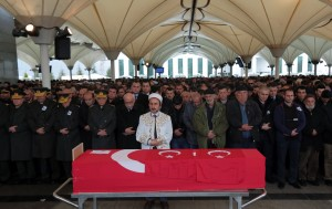 People stand by the Turkish flag-draped coffin of Murat Gul, 20, a security agent killed at Sunday's explosion during his funeral procession in Ankara, Turkey, Monday, March 14, 2016. A senior government official told The Associated Press that authorities believe the attack was carried out by two bombers, one of them a woman, and was the work of Kurdish militants. It was the second deadly attack blamed on Kurdish militants in the capital in the past month. (AP Photo/Burhan Ozbilici)