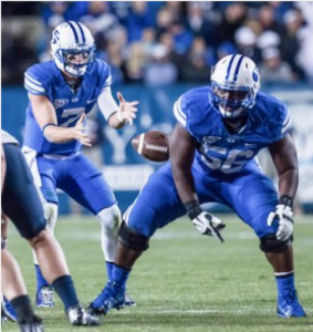 Tejan Koroma snaps the ball during a game in 2014. Koroma was welcomed back to the BYU football team by head coach Kalani Sitake on Tuesday. (Universe Archives)