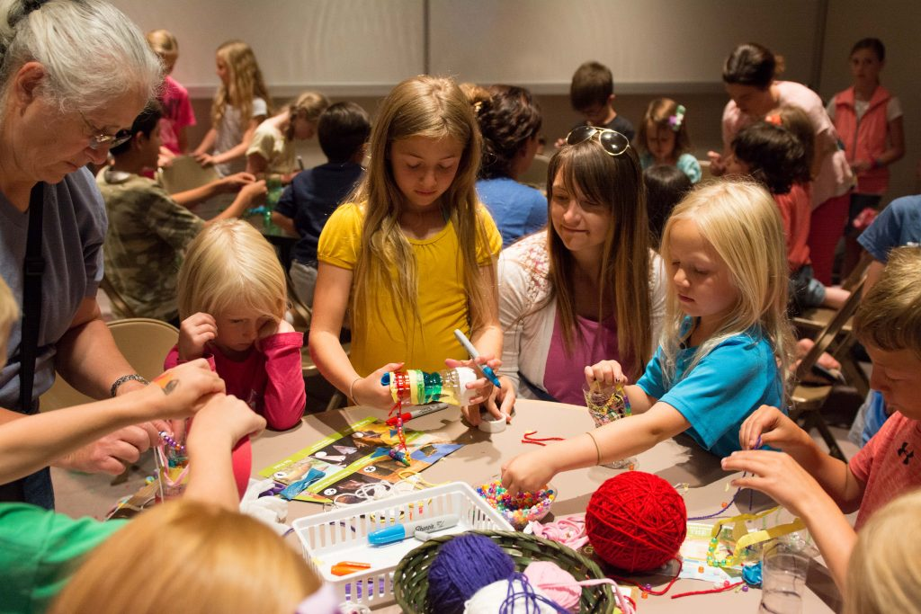Bucy, Larsen and Stevens families enjoy decorating and beading their recycled water bottles. (Natalie Saunders)