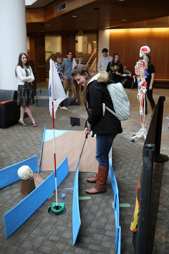 """A student plays mini-golf in the library atrium during last year's """"Love Your Library Week."""" This year's mini-golf holes will be specially designed by various library departments to showcase what they have to offer. (Roger Layton)"""
