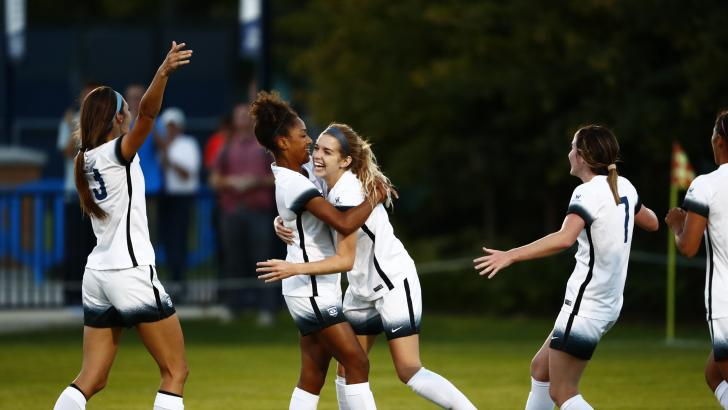 Paige Hunt Barker (center) celebrates with teammates after scoring a goal earlier this season. Hunt Barker is one of six women's soccer players to serve a LDS mission. (BYU Photo)