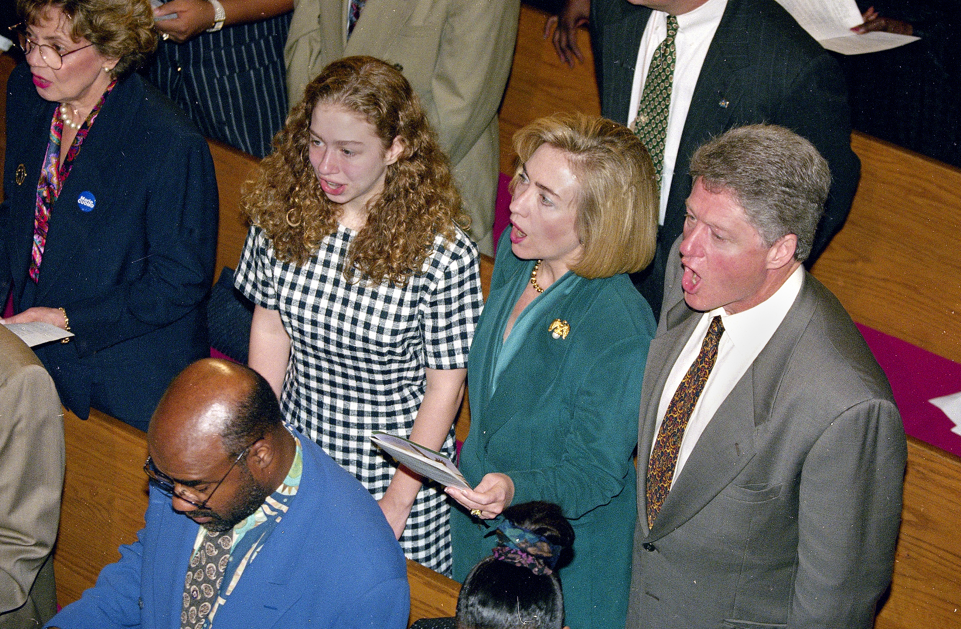 """FILE - In this Sept. 25, 1994 file photo, President Bill Clinton, first lady Hillary Rodham Clinton and their daughter, Chelsea, sing a hymn during church services at the Bethel African Methodist Church in the Harlem section of New York. Clinton is a lifelong Methodist. But the Rev. Bill Shillady _ who officiated at Chelsea Clinton's wedding, led a memorial service for Clinton's mother, Dorothy Rodham, and gave the closing benediction at the Democratic National Convention _ feels that many people don't really know how much her faith """"is a daily thing."""" (Associated Press)"""