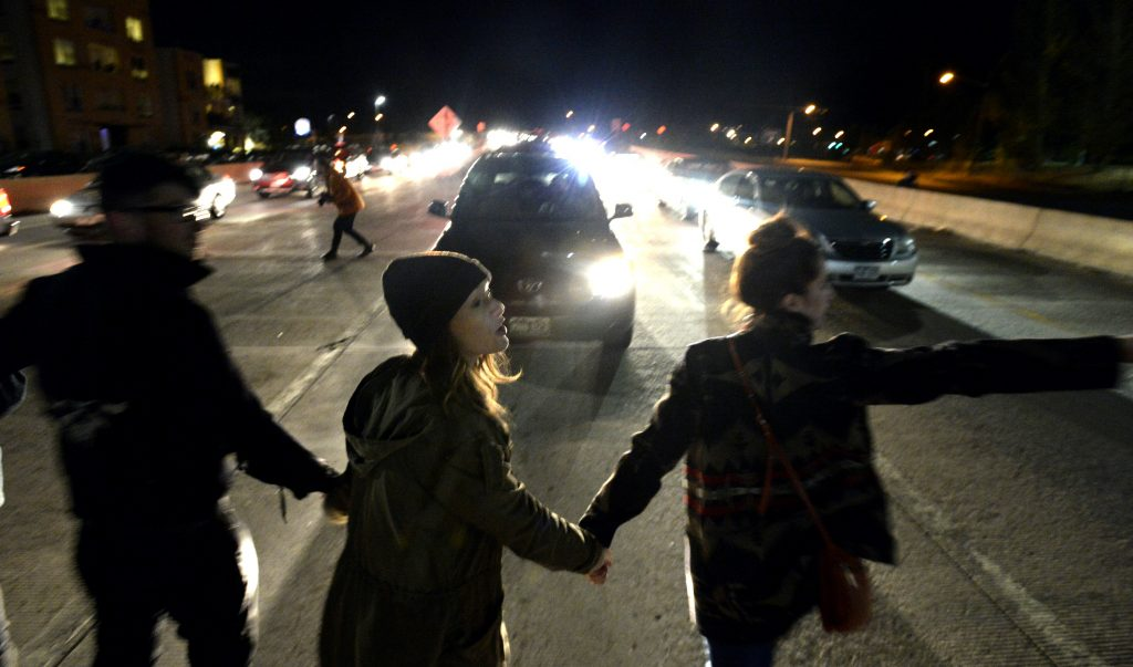 In this Thursday, Nov. 10, 2016 photo, marchers block traffic on highway US 36 just outside Boulder, Colo., during a protest in opposition of Donald Trump's presidential election victory. (Paul Aiken/Daily Camera via AP)