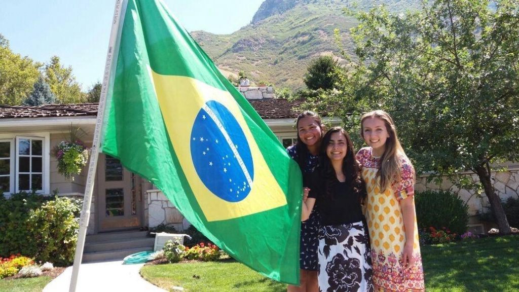 Rebeka Pires poses with her friends from the ELC outside a home with a Brazilian flag in Utah. (Rebeka Pires)