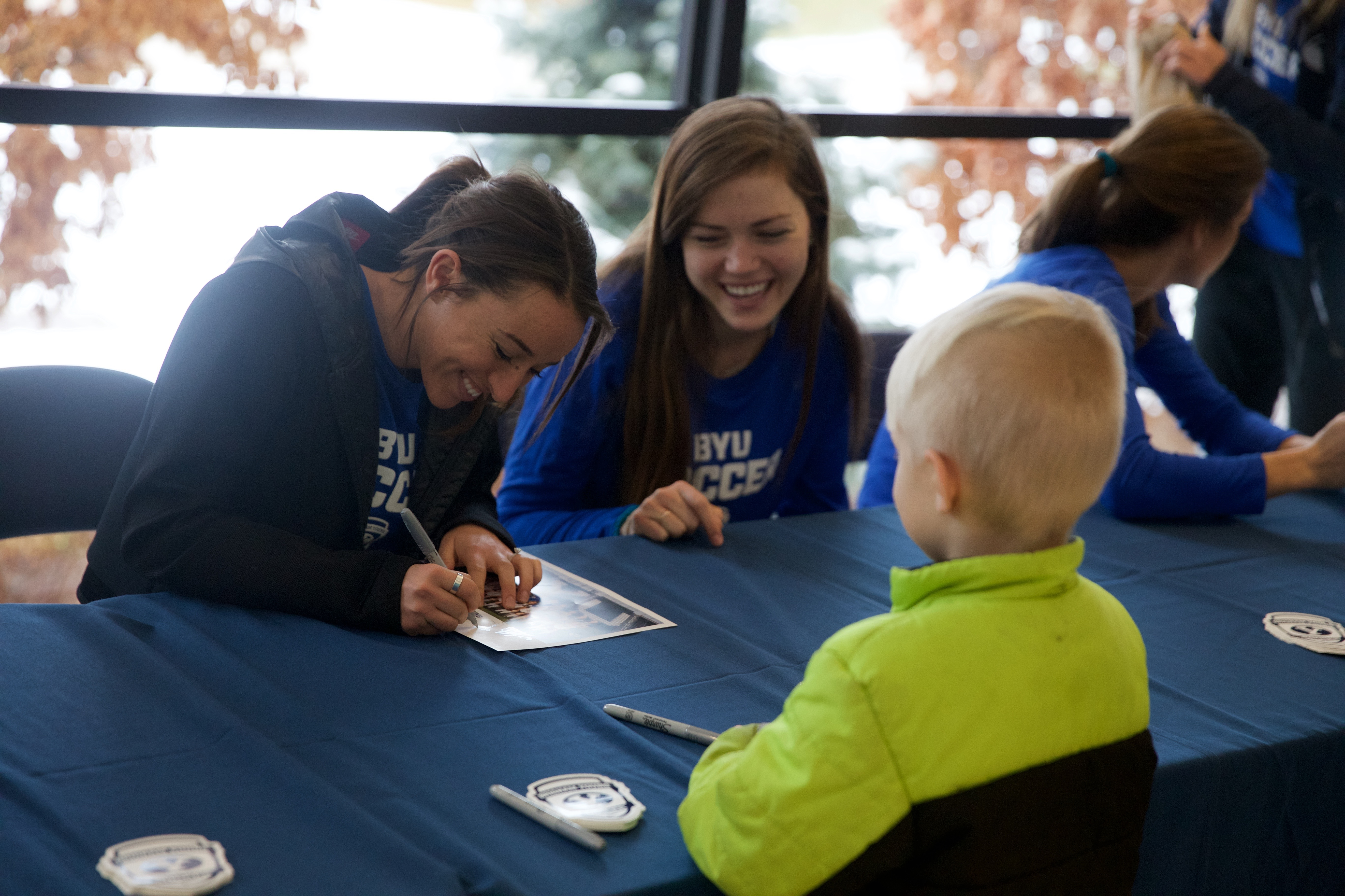Members of the BYU women's soccer team signs autographs for a young fan. (Maddi Driggs)